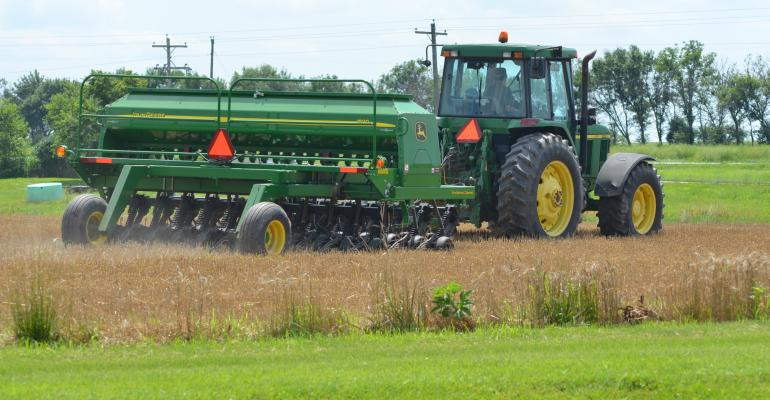 planter in field planting soybeans into wheat