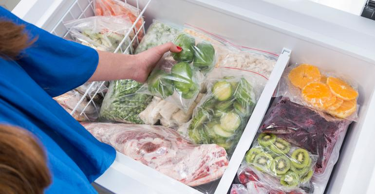 Woman putting bell peppers in fridge