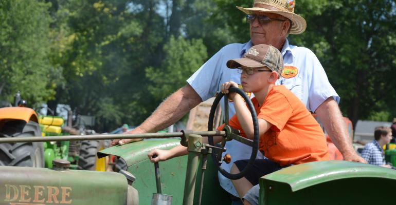 older man teaching young boy to drive tractor