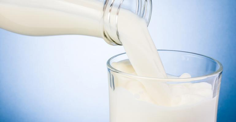 Close up of milk being poured into a glass from a bottle