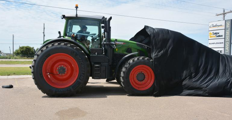 Workers pull the tarp covering the new Fendt 900 series tractor making a visit to the Lang Diesel dealership in Garden City in late July