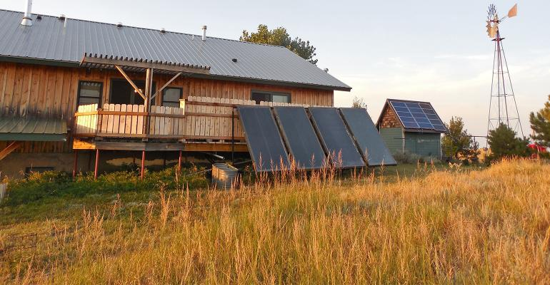 solar panels mounted on roof of battery house (right) and in front of ranch house