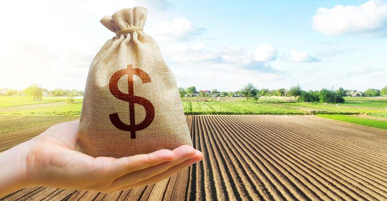 Hand holding bag of money with farm field in background