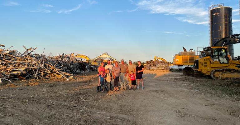 The Eachus family stands in the wreckage caused by a tornado