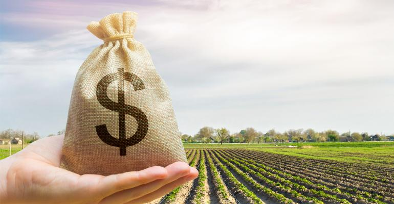 Hand holding bag of money with field of crops in background