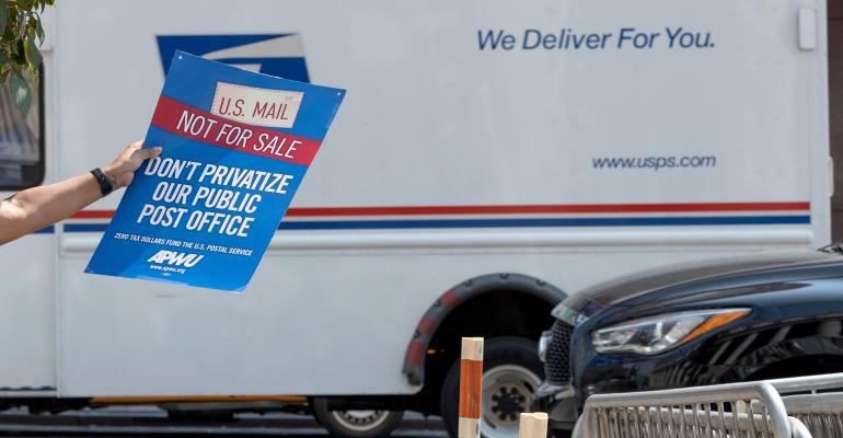 """A woman holds a """"U.S. mail not for sale"""" sign as a USPS mail truck drives past near at the """"Save The Post Office"""" rally"""
