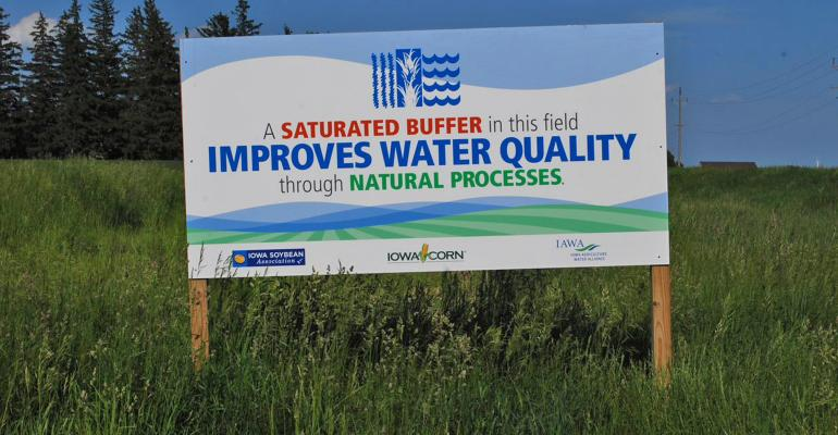 a sign promoting improved water quality in a field