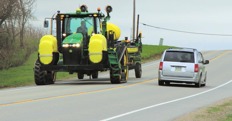 A sprayer and a car pass each other on a two-lane road