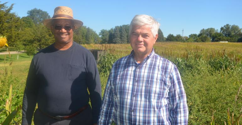 Bob Recker and Mike Cook stand in a field near Janesville.