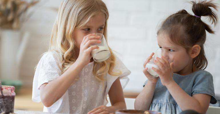 2 young girls drinking milk
