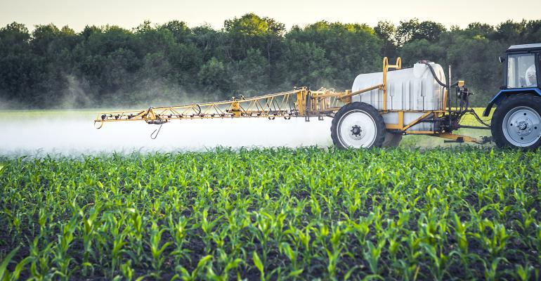 farmer on a tractor with a trailed sprayer makes fertilizer for young corn in the form of microdroplets.