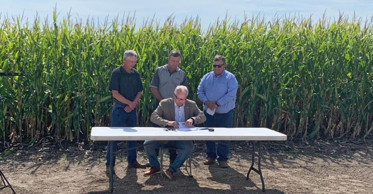 Minnesota Gov. Tim Walz, seated at table, signs executive order establishing Governor's Biofuels Council, flanked by Gary Anderson, Brian Thalmann and Thom Petersen
