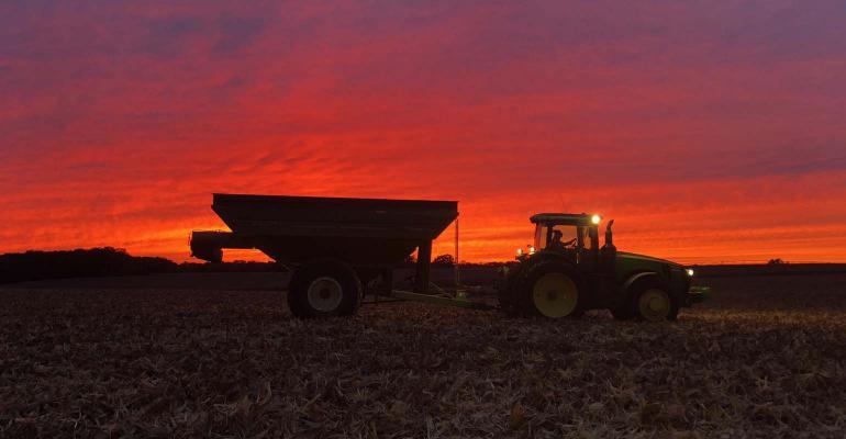 photo of tractor with grain cart in evening glow