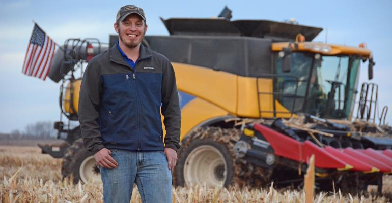 Ryan Atherton standing in front of combine