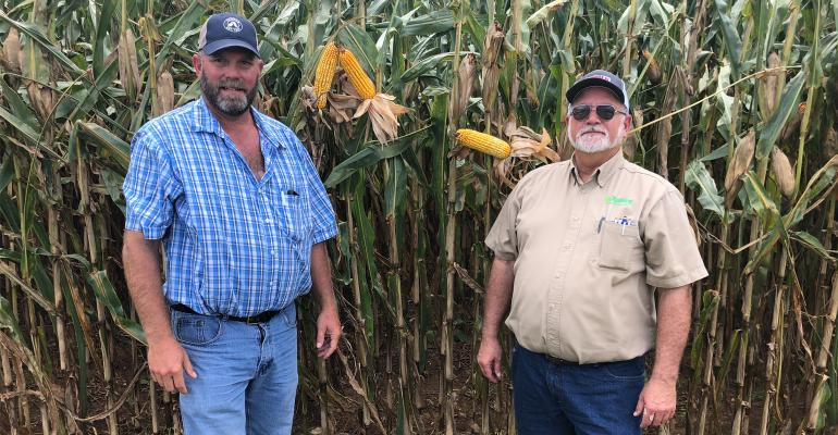 Drew Haines and his agronomist Grant Troop stand together beside corn field