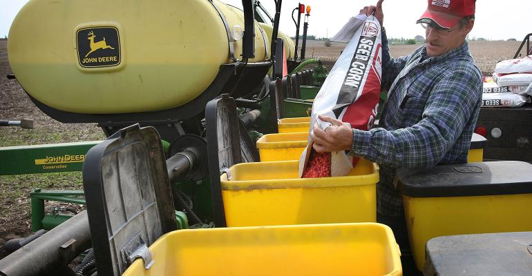 farmer filling planter with seed corn