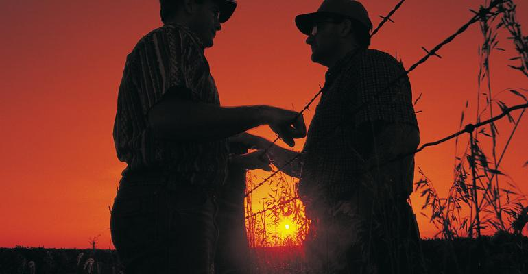 two farmers talking over barbed wire fence at sunset