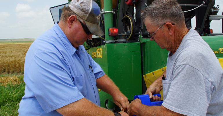 Senior agricultural technicians Clayton Seaman and Ken Rohleder bag seed wheat at the K-State Research Station at Fort Hays State University