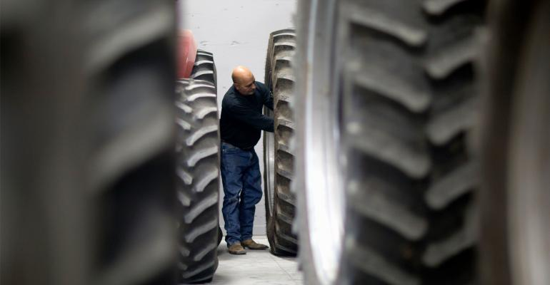 Framed by tractor tires, a mature farmer works on his equipment.