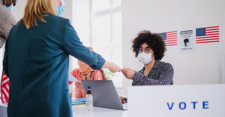 People with face masks voting.