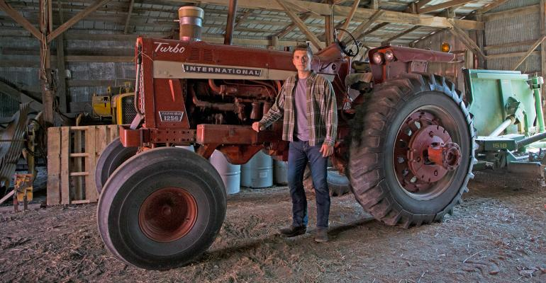Zebediah Davis standing in front of International 1256 tractor