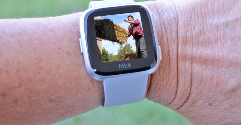 Fitbit with picture of farmer tossing hay bale