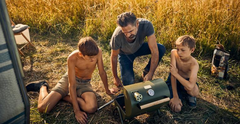 Father with two boys operating a small grill while out camping