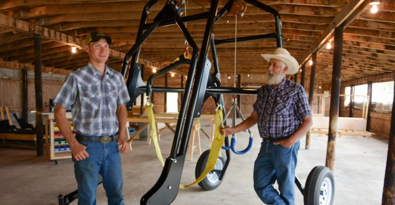 E.J. Swihart and his cousin Roger Swihart stand beside their Cow Crane