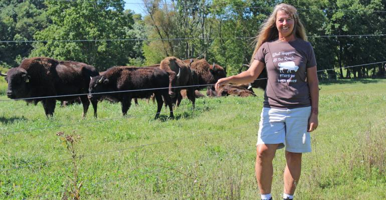 Carie Starr standing in field with bison