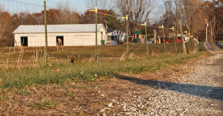 white farm building, wire fence and gravel driveway
