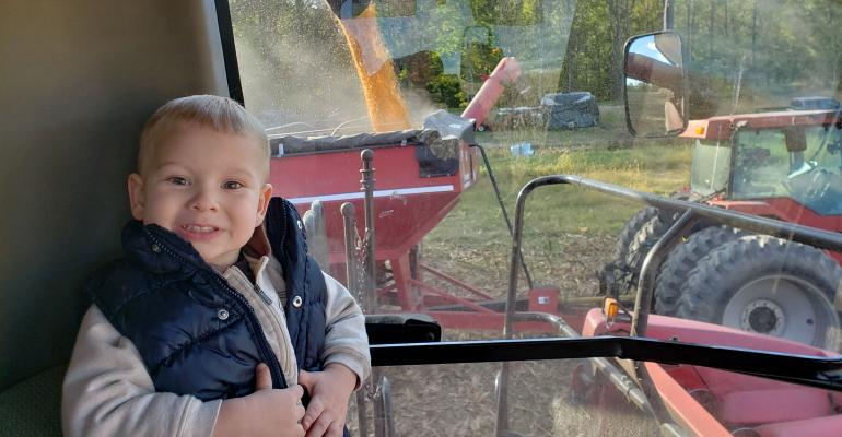 Cole Rescovac sits in the cab of a combine