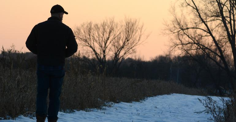 silhouette of man looking off into the distance at dusk