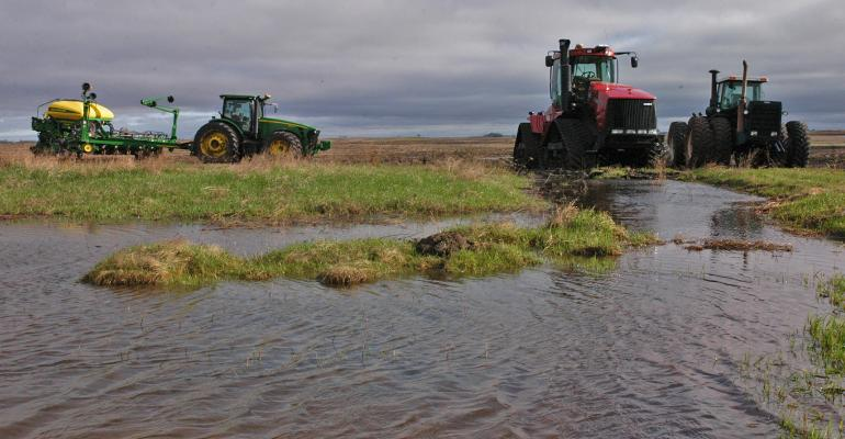 Tractors and planters sit idle at the edge of field that has standing water