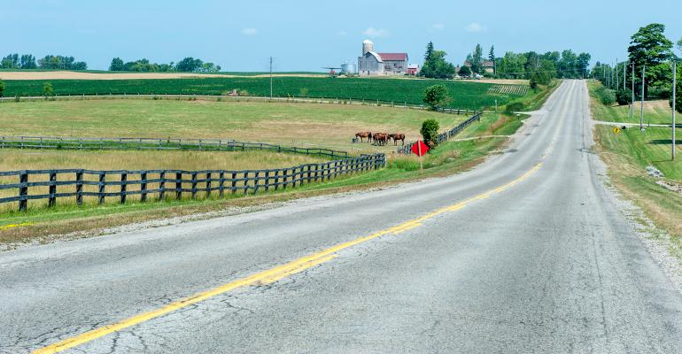 rural country road through farm land with silos, barn and horses