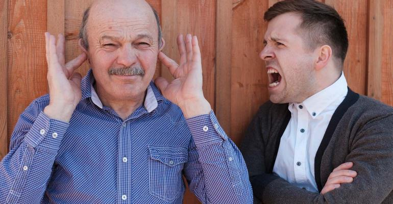 Man with hands in his ears while adult son hollers next to him.