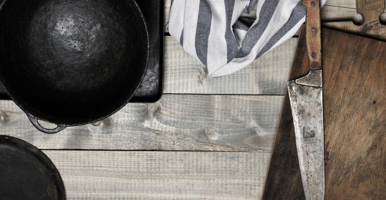 cast iron, knife and cutting board against wood background