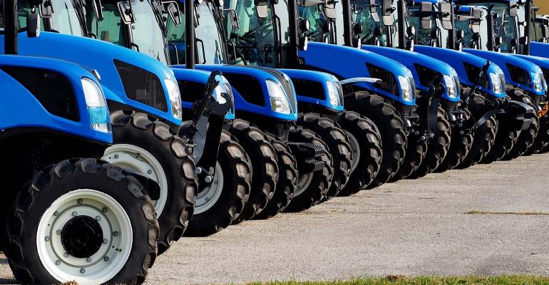 Close up of brand new blue tractors,  side by side, in a long line .