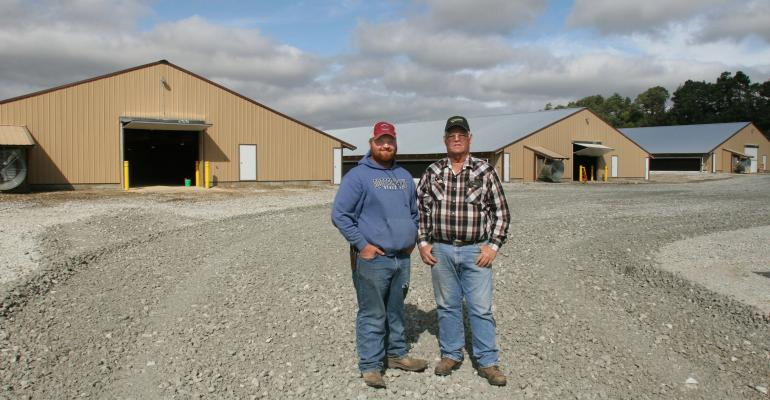 Colten Schafersman and his grandfather, John Snover in front of the newly-constructed pullet and rooster barns