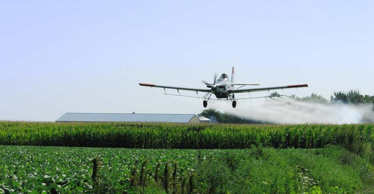 Cropduster flying over the corn and soybean field.