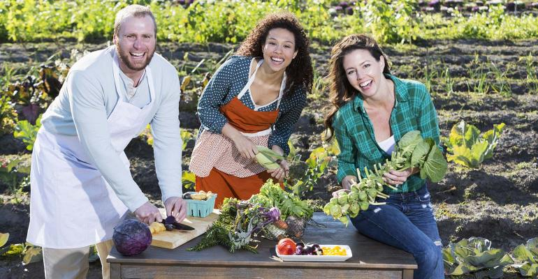 A group of three people preparing fresh, organic vegetables on a table beside a field of crops.  They are part of the farm-to-table or farm-to-fork movement in which locally grown food is processed and prepared for local customers.