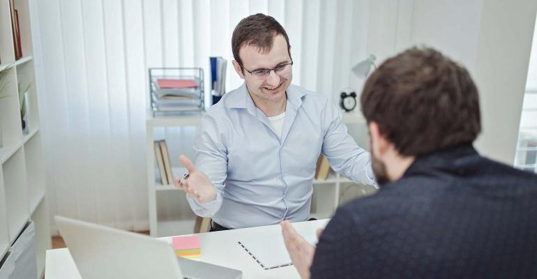 Image of two young men discussing work in meeting
