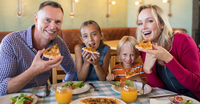 Portrait of happy family having pizza at restaurant