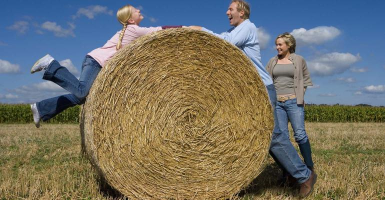 Father playing with daughter over round bale.
