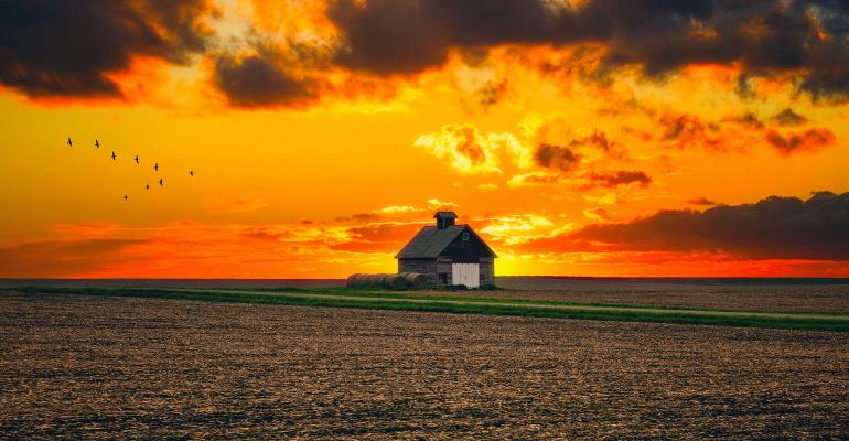 One rural barn in the middle of field landscape on the sunset and stormy sky background