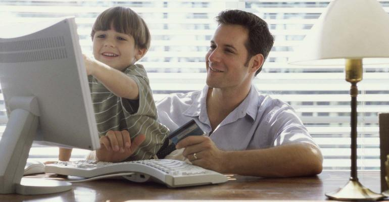 Father and son sitting at desktop computer