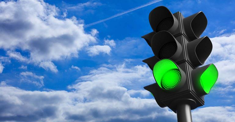 green traffic light concept; green go signal on blue sky background