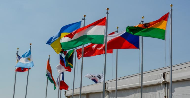 Many nations' colorful flags fly above the International Trade Center at the Farm Progress Show
