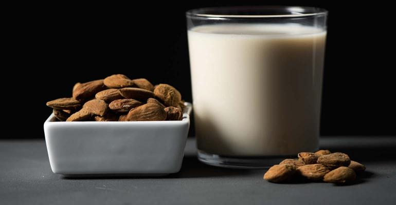 closeup of a white ceramic bowl with almonds and a glass of almond milk on a gray rustic wooden table, against a black background
