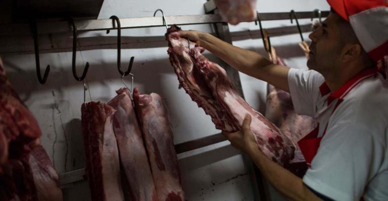 Butcher hanging up sides of meat in freezer.