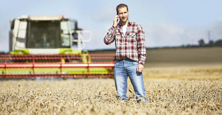 Farmer On Phone in front of Combine